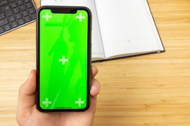 Immagine del modello della mano che tiene telefono cellulare nero con lo schermo verde sul tavolo dell'ufficio sui precedenti con gli strumenti della cancelleria