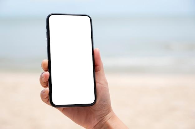 Immagine mockup di una mano che tiene e mostra un telefono cellulare nero con schermo desktop vuoto in riva al mare