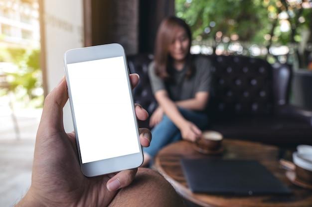 Immagine del modello della mano che tiene telefono cellulare bianco con lo schermo in bianco in caffè