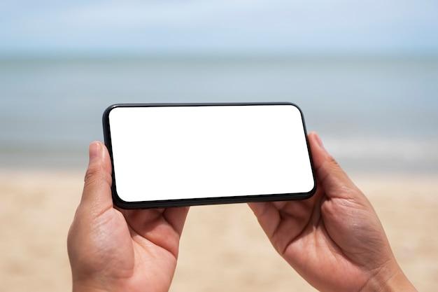 Immagine mockup di mani che tengono un telefono cellulare nero con schermo desktop vuoto in riva al mare