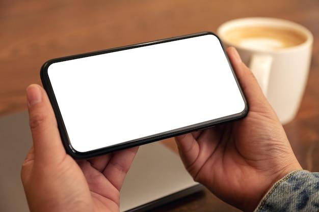 Immagine del modello delle mani che tengono il telefono cellulare nero con lo schermo del desktop vuoto orizzontalmente con la tazza di caffè sul tavolo