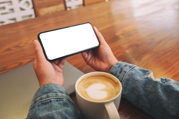 Immagine del modello delle mani che tengono il telefono cellulare nero con lo schermo del desktop vuoto orizzontalmente con il computer portatile e la tazza di caffè sul tavolo
