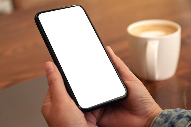Immagine di mockup delle mani che tengono il telefono cellulare nero con schermo desktop vuoto con laptop e tazza di caffè sul tavolo
