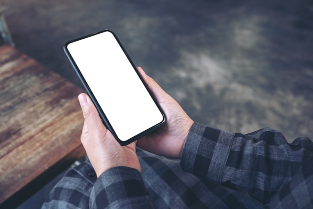 Immagine di mockup delle mani che tengono il telefono cellulare nero con schermo bianco vuoto nella caffetteria vintage