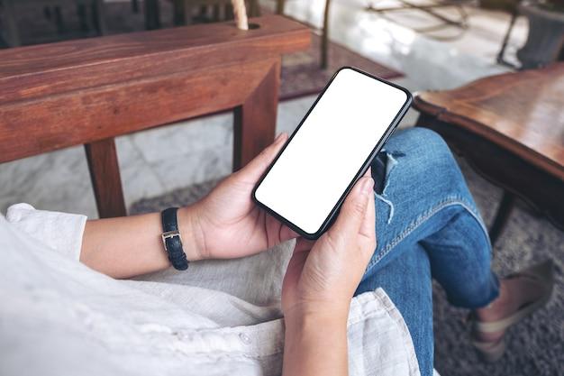 Immagine del modello delle mani che tengono il telefono cellulare nero con schermo bianco vuoto mentre è seduto nella caffetteria