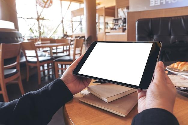 Immagine del modello delle mani che tengono il pc nero della compressa con lo schermo in bianco con il taccuino e il pane sulla tavola di legno nella caffetteria