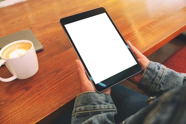 Immagine del modello delle mani che tengono il pc nero della compressa con lo schermo bianco in bianco con la tazza di caffè sulla tavola di legno