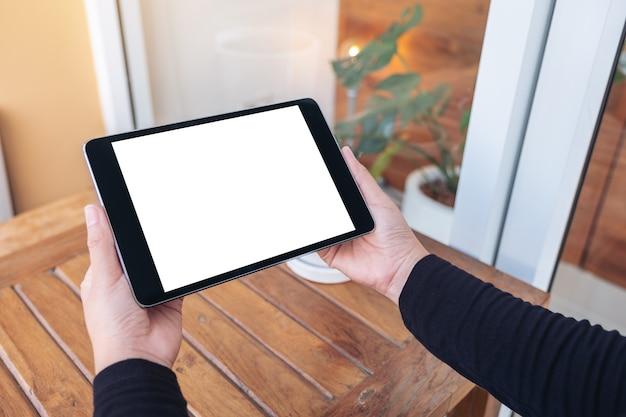 Immagine del modello delle mani che tengono e che esaminano il pc nero della compressa con lo schermo bianco vuoto