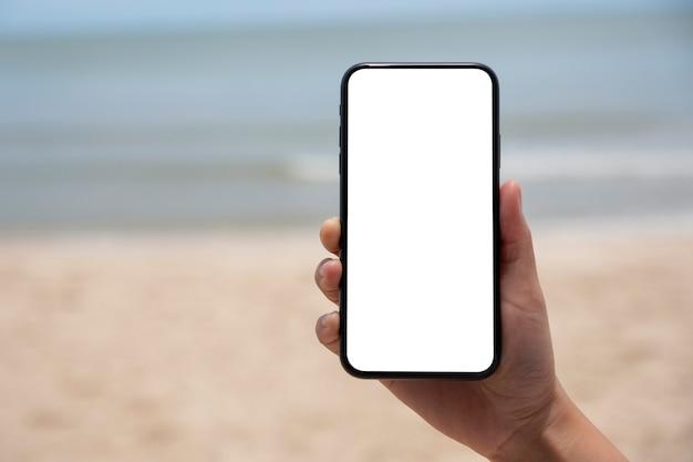 Immagine mockup di mani che tengono e mostrano un telefono cellulare nero con schermo desktop vuoto in riva al mare