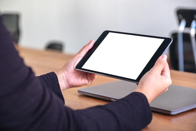 Immagine di mockup di mani che tengono e utilizzando tablet pc nero con schermo desktop bianco vuoto