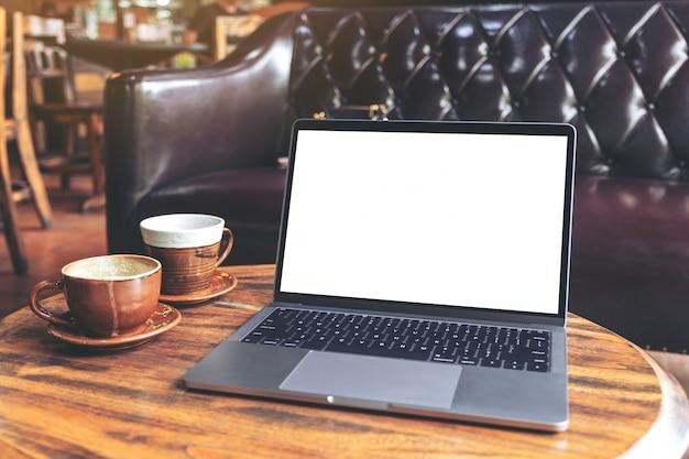 Immagine del modello del computer portatile con lo schermo da tavolino bianco in bianco e la tazza di caffè sulla tavola di legno in caffè