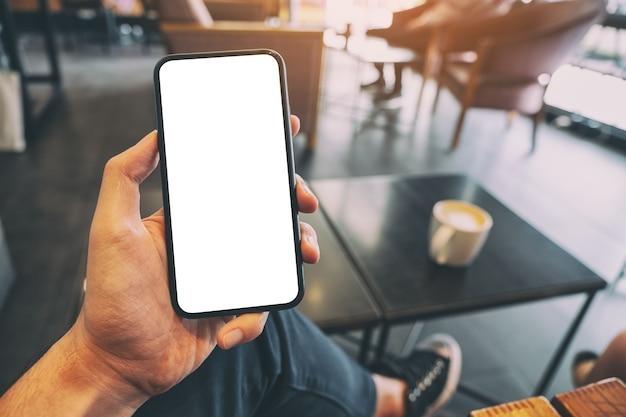 Immagine del modello della mano di un uomo che tiene il telefono cellulare nero con schermo vuoto con una tazza di caffè sul tavolo nella caffetteria