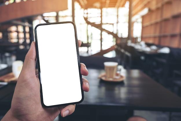 Immagine di mockup della mano di un uomo che tiene il telefono cellulare nero con schermo vuoto con un bicchiere di caffè sulla tavola di legno nella caffetteria
