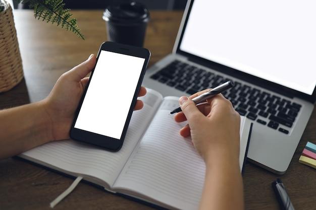 Immagine del modello della mano della donna che tiene lo smartphone dello schermo desktop bianco in bianco con il computer portatile sulla tavola mentre scrive la sua idea sul taccuino. acquisti online, marketing digitale sul cellulare