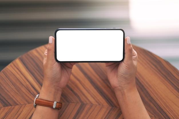 Immagine del modello di una donna che tiene il telefono cellulare nero con lo schermo del desktop bianco vuoto orizzontalmente con il fondo della tavola in legno