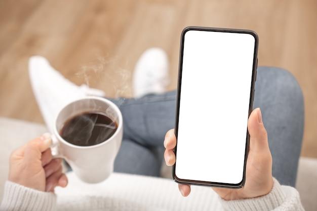 Immagine del modello della donna che tiene il telefono cellulare nero con lo schermo bianco vuoto nella caffetteria.