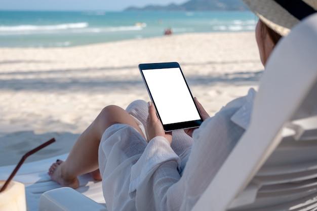 Immagine di mockup di una donna che tiene un tablet pc nero con schermo desktop vuoto mentre si sdraia sulla sedia a sdraio sulla spiaggia