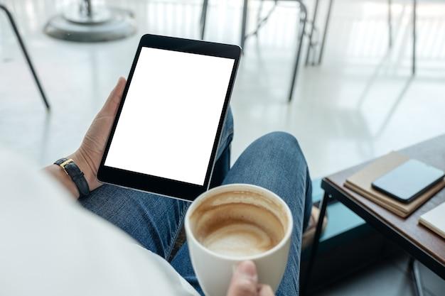Immagine del modello di una donna che tiene un tablet pc nero con schermo vuoto mentre beve il caffè nella caffetteria