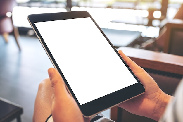 Immagine del modello di una donna che tiene un tablet pc nero con schermo bianco vuoto mentre è seduto nella caffetteria