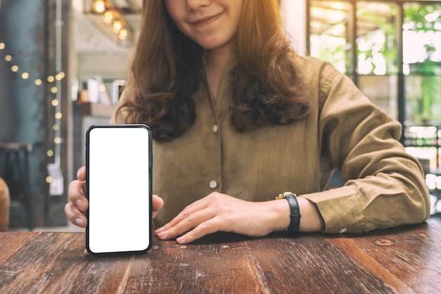 Immagine del modello di una donna che tiene e che mostra il telefono cellulare nero con lo schermo bianco vuoto sul tavolo nella caffetteria
