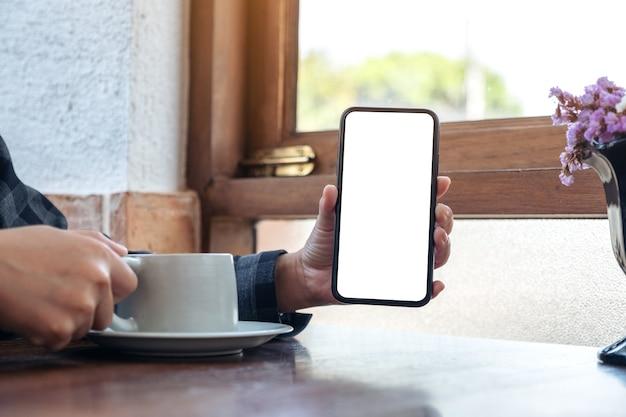 Immagine del modello di una donna che tiene e che mostra il telefono cellulare nero con lo schermo bianco vuoto mentre beve il caffè nella caffetteria