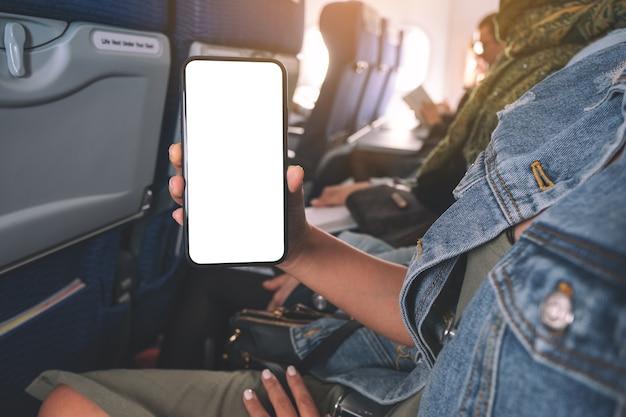 Immagine del modello della donna che tiene e che mostra uno smart phone nero con lo schermo del desktop vuoto in cabina