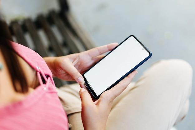 Immagine mockup di una donna che tiene in mano uno smartphone con schermo vuoto all'aperto