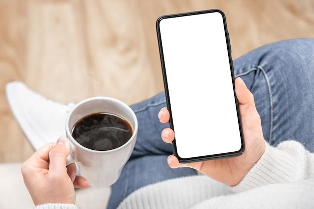 Immagine del modello di una donna che tiene e utilizzando il telefono cellulare nero con lo schermo del desktop vuoto
