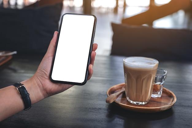 Immagine di mockup della mano di una donna che tiene il telefono cellulare nero con schermo vuoto con un bicchiere di caffè sulla tavola di legno nella caffetteria