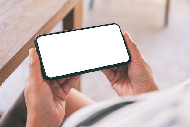 Immagine del modello delle mani della donna che tengono il telefono cellulare nero con lo schermo bianco vuoto orizzontalmente nella caffetteria