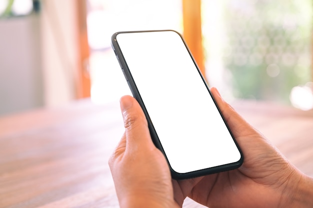 Immagine del modello delle mani della donna che tengono il telefono cellulare nero con lo schermo bianco in bianco sulla tavola di legno