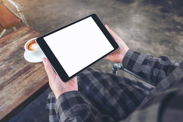 Immagine del modello delle mani della donna che tengono il pc nero della compressa con lo schermo in bianco con la tazza di caffè