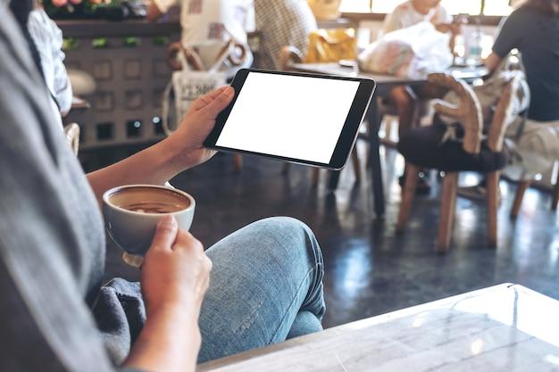 Immagine del modello delle mani della donna che tengono il pc nero della compressa con lo schermo in bianco