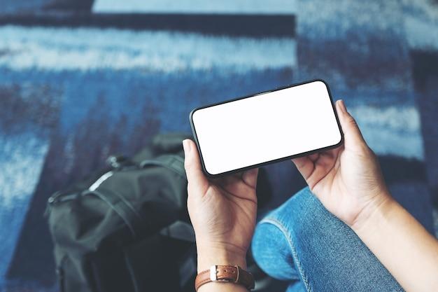 Immagine mockup delle mani di una donna che tiene e usa un telefono cellulare nero con schermo vuoto mentre è seduta in aeroporto