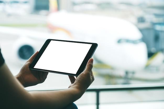 Immagine mockup delle mani di una donna che tiene e usa un tablet pc nero con schermo bianco vuoto mentre è seduta in aeroporto