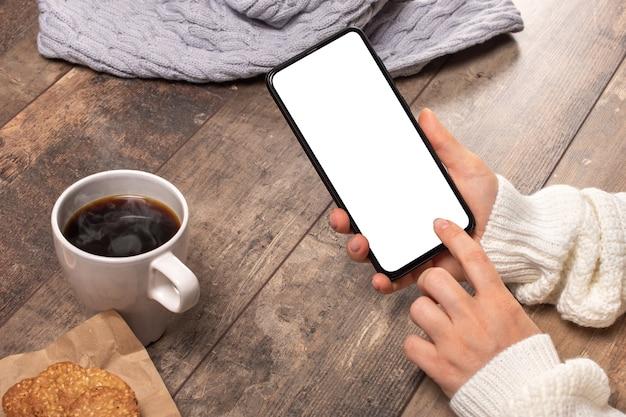 Immagine del modello delle mani della donna che tengono il telefono cellulare bianco con lo schermo in bianco sulla tavola di legno d'annata