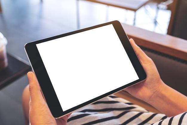 Immagine di mockup di una donna seduta e che tiene un tablet pc nero con lo schermo del desktop bianco vuoto orizzontalmente