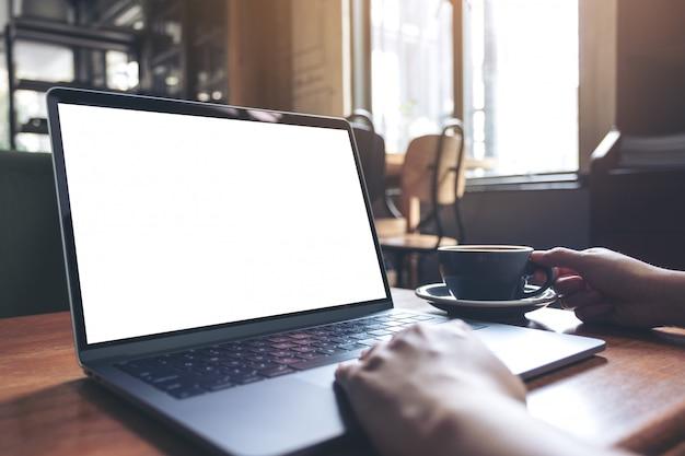 Immagine del modello di una donna che utilizza computer portatile con lo schermo da tavolino bianco in bianco mentre bevendo caffè caldo sulla tavola di legno nel caffè