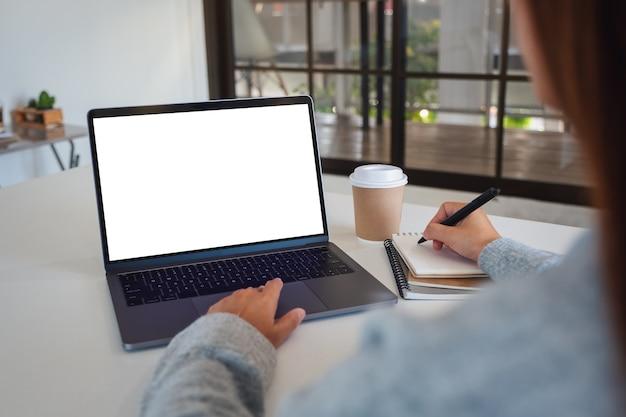 Immagine mockup di una donna che utilizza un laptop con uno schermo desktop bianco vuoto mentre scrive su un notebook in ufficio