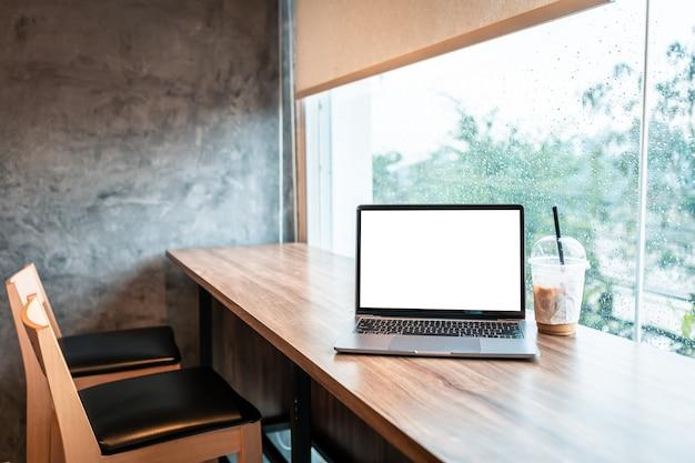 Mockup di computer portatile con schermo vuoto con caffè isolato su scrivania in legno in una caffetteria come lo sfondo, schermo bianco