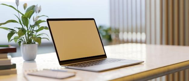 Mockup dello schermo di un laptop su una scrivania con decorazioni per la casa in uno spazio di lavoro moderno ufficio interno 3d