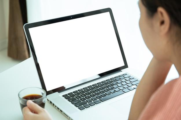 Schermo del computer portatile del modello isolato con il percorso di residuo della potatura meccanica. giovane donna asiatica che lavora a casa in soggiorno, giovane donna d'affari che utilizza computer portatile - notebook per navigare in internet.