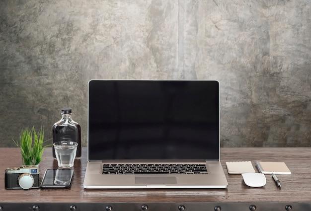 Mockup portatile con schermo nero e supplise sul tavolo di legno.