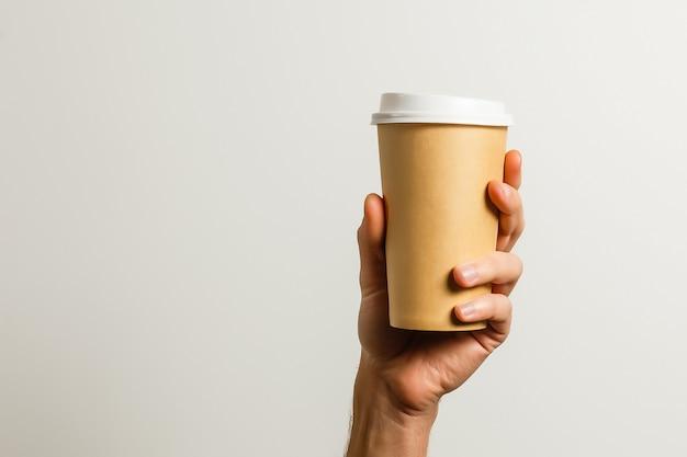 Mockup di mano maschile che tiene una tazza di carta da caffè isolata su sfondo grigio chiaro