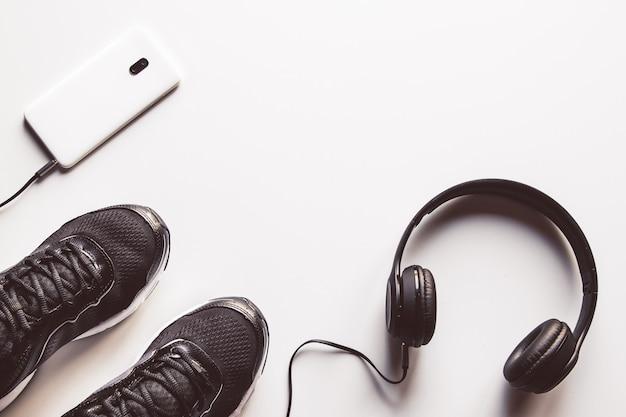 Cellulare mockup con auricolare e scarpe da corsa
