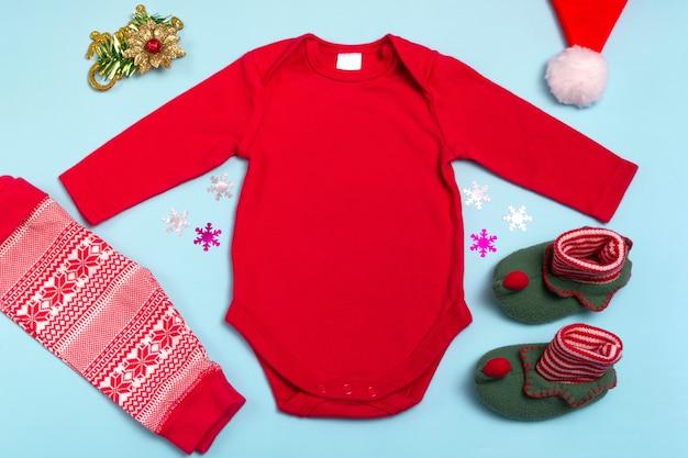 Mockup di body a maniche lunghe rosso di capodanno su sfondo blu, decorato con calze, pantaloni rossi e decorazioni per l'albero di natale, vista dall'alto. mockup per la progettazione e il posizionamento di loghi
