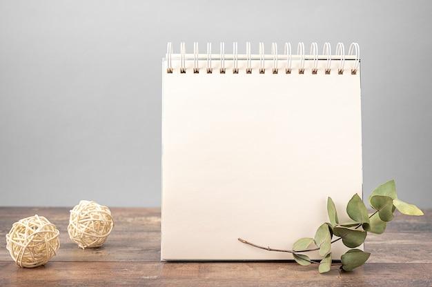 Il modello del taccuino con il foglio di carta in bianco bianco sta sulla tavola di legno