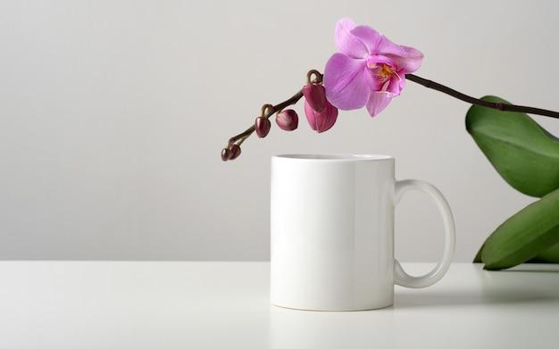 Mockup di una tazza bianca su un tavolo con decorazioni di fiori di orchidea in un interno minimalista