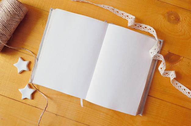 Il modello ha aperto il blocco note in bianco con le matite variopinte sulla tavola di legno. foto piatta, vista dall'alto, mock up