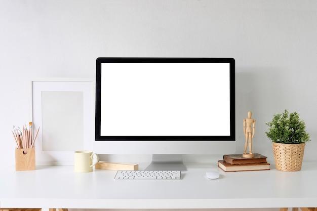 Computer del pc del modello sugli articoli per ufficio bianchi del progettista e della tavola sullo scrittorio con l'area di lavoro.